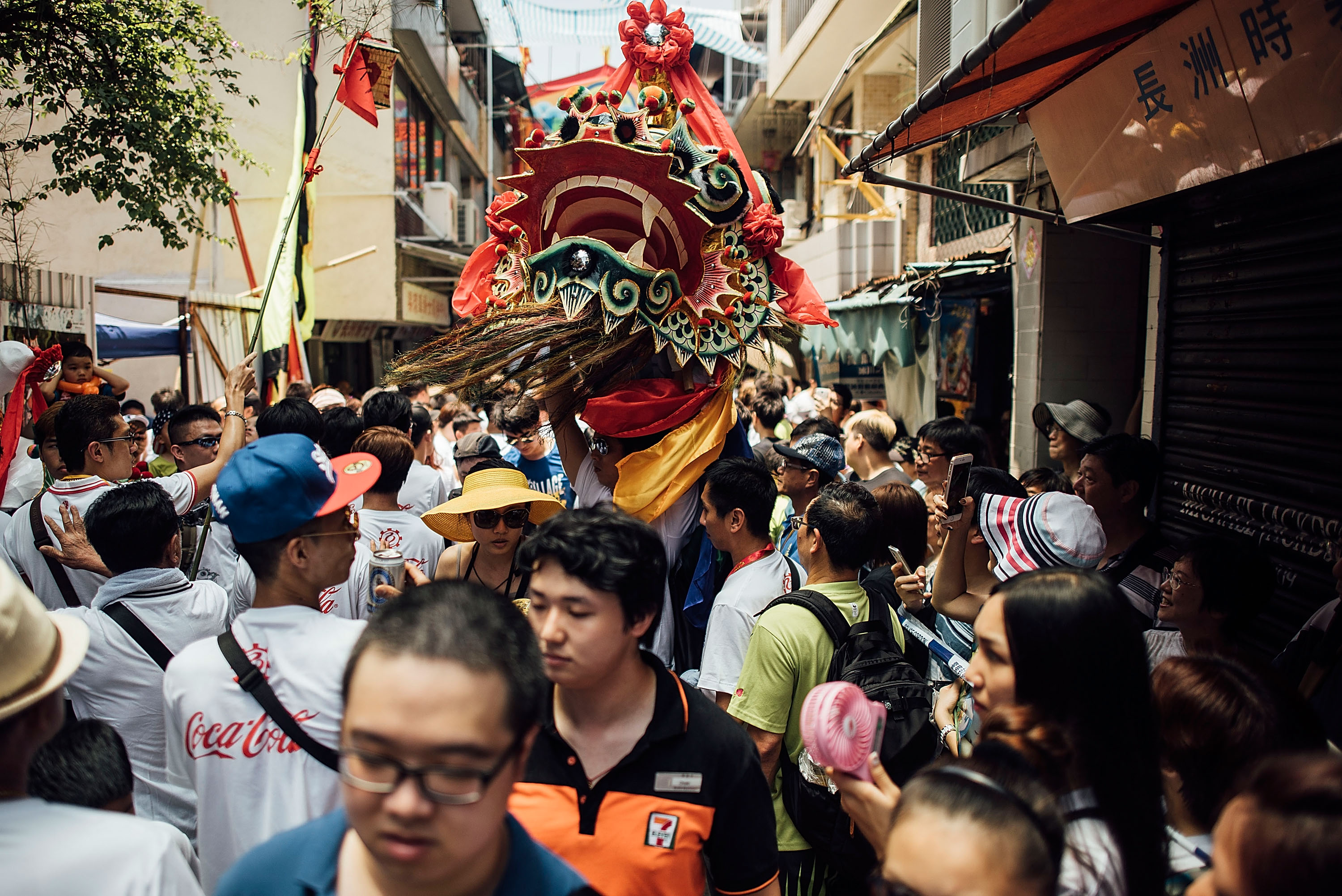 HONG KONG - MAY 25:  Participants take part in a dragon dance during Piu Sik (Floating Colours) Parade at Bun Festival in Cheung Chau Island on May 25, 2015 in Hong Kong. One of Hong Kong's most colourful cultural celebration events, Cheung Chau Bun Festival, will be staged on 25 May 2015 (Monday) until 26th May 2015 midnight (Tuesday). The festival has over 100 years of history. Every year, thousands of people descend upon the tiny island for The Piu Sik (Floating Colours) Parade, Lucky Bun (Ping On Bun) and The Bun Scrambling Competition, the ancient custom during the festival. The tradition has been passed down for generations. To ensure the tradition keeps passing on, every year, Cheung Chau Islanders fuse the new elements with the custom to draw the attention from the young. This year, 'K-Pop stars' will be featured by one of the Piu Sik parade teams, the first-ever 'Ping On (Lucky) Macaron' with Chinese tea favour is invented, and more to be found out on the island.  (Photo by Anthony Kwan/Getty Images for Hong Kong Images)