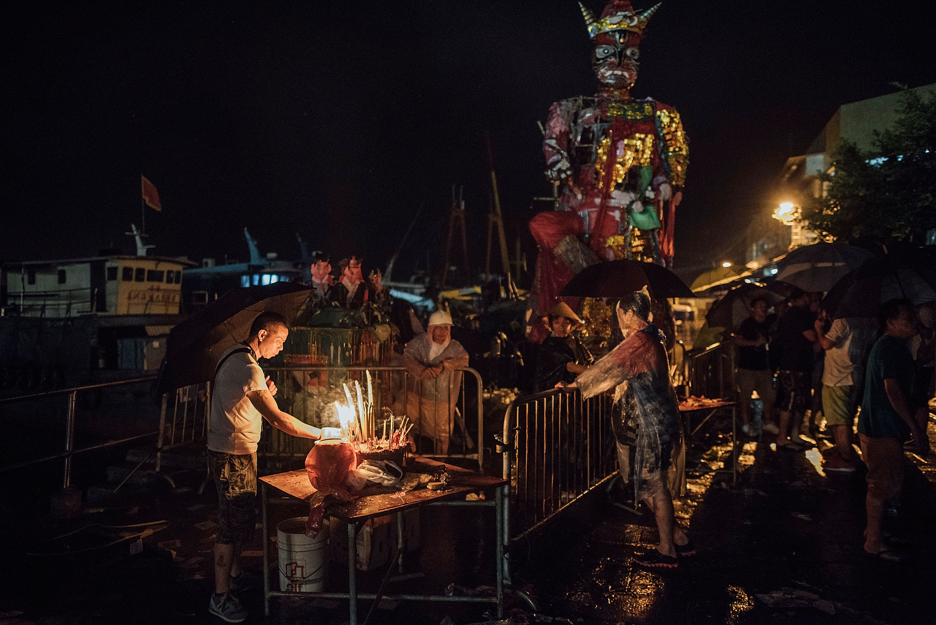 "HONG KONG - MAY 25:  People make offerings to the ""Demon God"" during the Bun Festival on May 25, 2015 on Cheung Chau Island in Hong Kong. One of Hong Kong's most colourful cultural celebration events, Cheung Chau Bun Festival, will be staged on 25 May 2015 (Monday) until 26th May 2015 midnight (Tuesday). The festival has over 100 years of history. Every year, thousands of people descend upon the tiny island for The Piu Sik (Floating Colours) Parade, Lucky Bun (Ping On Bun) and The Bun Scrambling Competition, the ancient custom during the festival. The tradition has been passed down for generations. To ensure the tradition keeps passing on, every year, Cheung Chau Islanders fuse the new elements with the custom to draw the attention from the young. This year, 'K-Pop stars' will be featured by one of the Piu Sik parade teams, the first-ever 'Ping On (Lucky) Macaron' with Chinese tea favour is invented, and more to be found out on the island.  (Photo by Anthony Kwan/Getty Images for Hong Kong Images)"