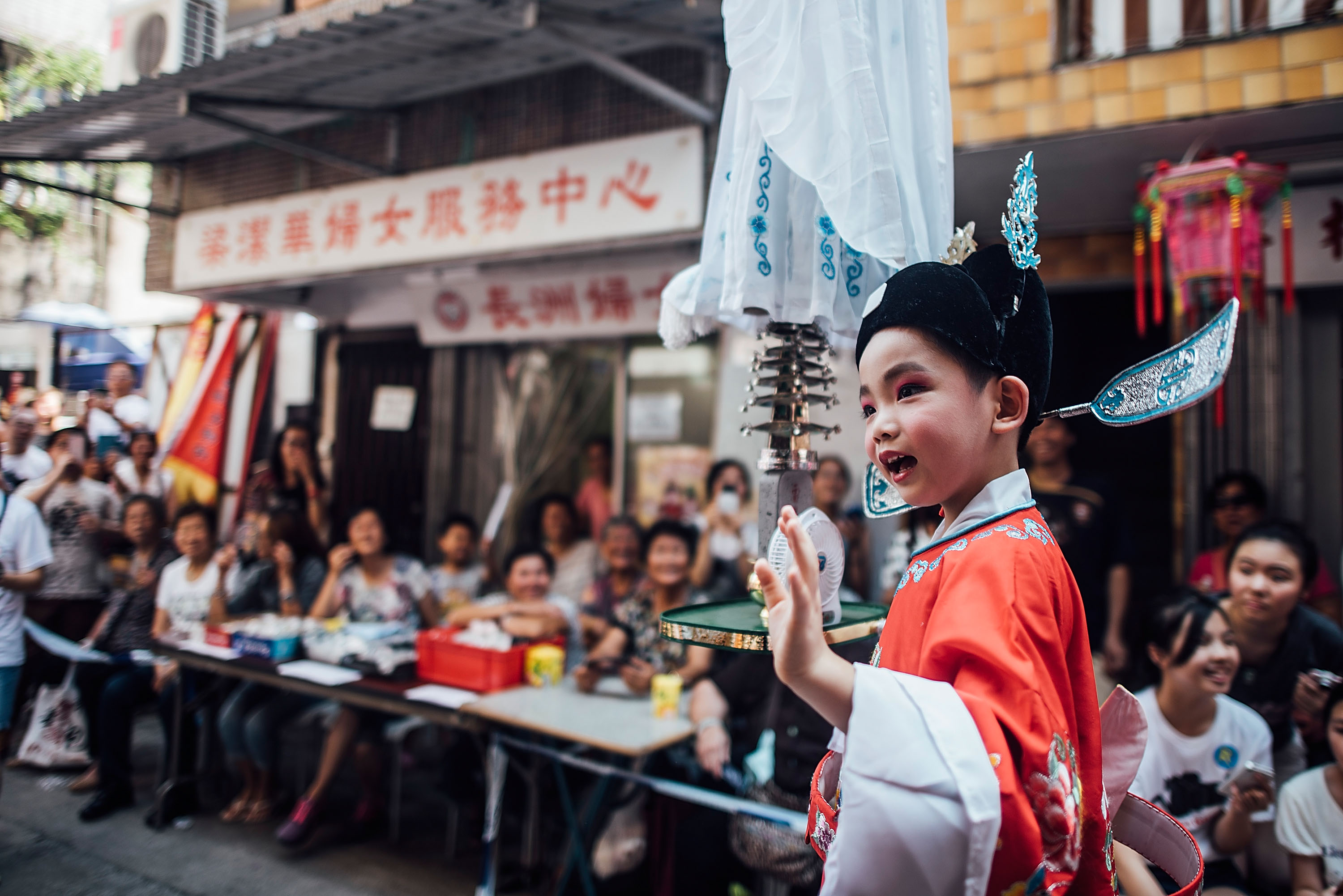HONG KONG - MAY 25:  A child dressed in costume performs on a float during Piu Sik (Floating Colours) Parade at Bun Festival in Cheung Chau Island on May 25, 2015 in Hong Kong. One of Hong Kong's most colourful cultural celebration events, Cheung Chau Bun Festival, will be staged on 25 May 2015 (Monday) until 26th May 2015 midnight (Tuesday). The festival has over 100 years of history. Every year, thousands of people descend upon the tiny island for The Piu Sik (Floating Colours) Parade, Lucky Bun (Ping On Bun) and The Bun Scrambling Competition, the ancient custom during the festival. The tradition has been passed down for generations. To ensure the tradition keeps passing on, every year, Cheung Chau Islanders fuse the new elements with the custom to draw the attention from the young. This year, 'K-Pop stars' will be featured by one of the Piu Sik parade teams, the first-ever 'Ping On (Lucky) Macaron' with Chinese tea favour is invented, and more to be found out on the island.  (Photo by Anthony Kwan/Getty Images for Hong Kong Images)