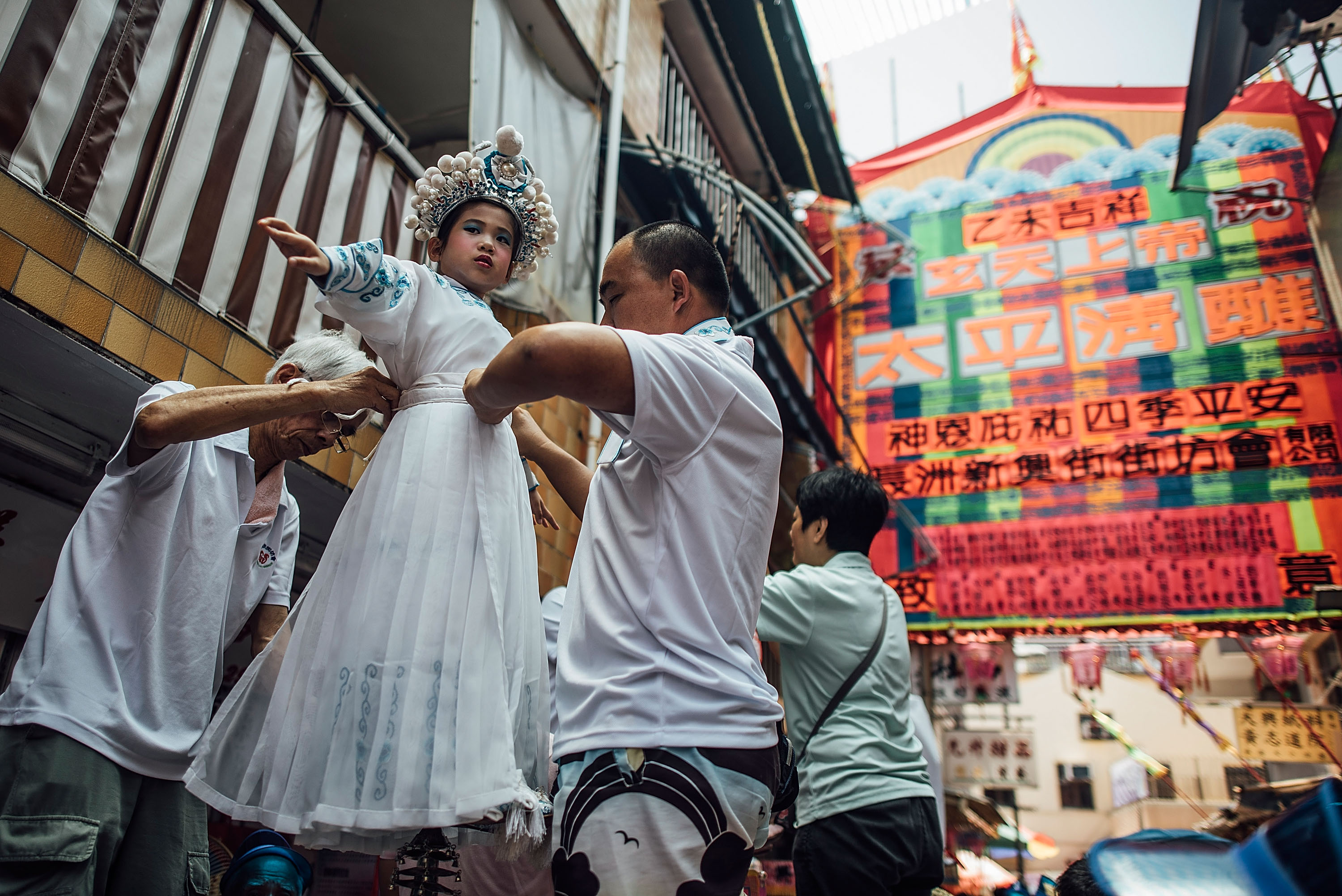 HONG KONG - MAY 25:  Children prepare for the Piu Sik (Floating Colours) Parade at Bun Festival in Cheung Chau Island on May 25, 2015 in Hong Kong. One of Hong Kong's most colourful cultural celebration events, Cheung Chau Bun Festival, will be staged on 25 May 2015 (Monday) until 26th May 2015 midnight (Tuesday). The festival has over 100 years of history. Every year, thousands of people descend upon the tiny island for The Piu Sik (Floating Colours) Parade, Lucky Bun (Ping On Bun) and The Bun Scrambling Competition, the ancient custom during the festival. The tradition has been passed down for generations. To ensure the tradition keeps passing on, every year, Cheung Chau Islanders fuse the new elements with the custom to draw the attention from the young. This year, 'K-Pop stars' will be featured by one of the Piu Sik parade teams, the first-ever 'Ping On (Lucky) Macaron' with Chinese tea favour is invented, and more to be found out on the island.  (Photo by Anthony Kwan/Getty Images for Hong Kong Images)