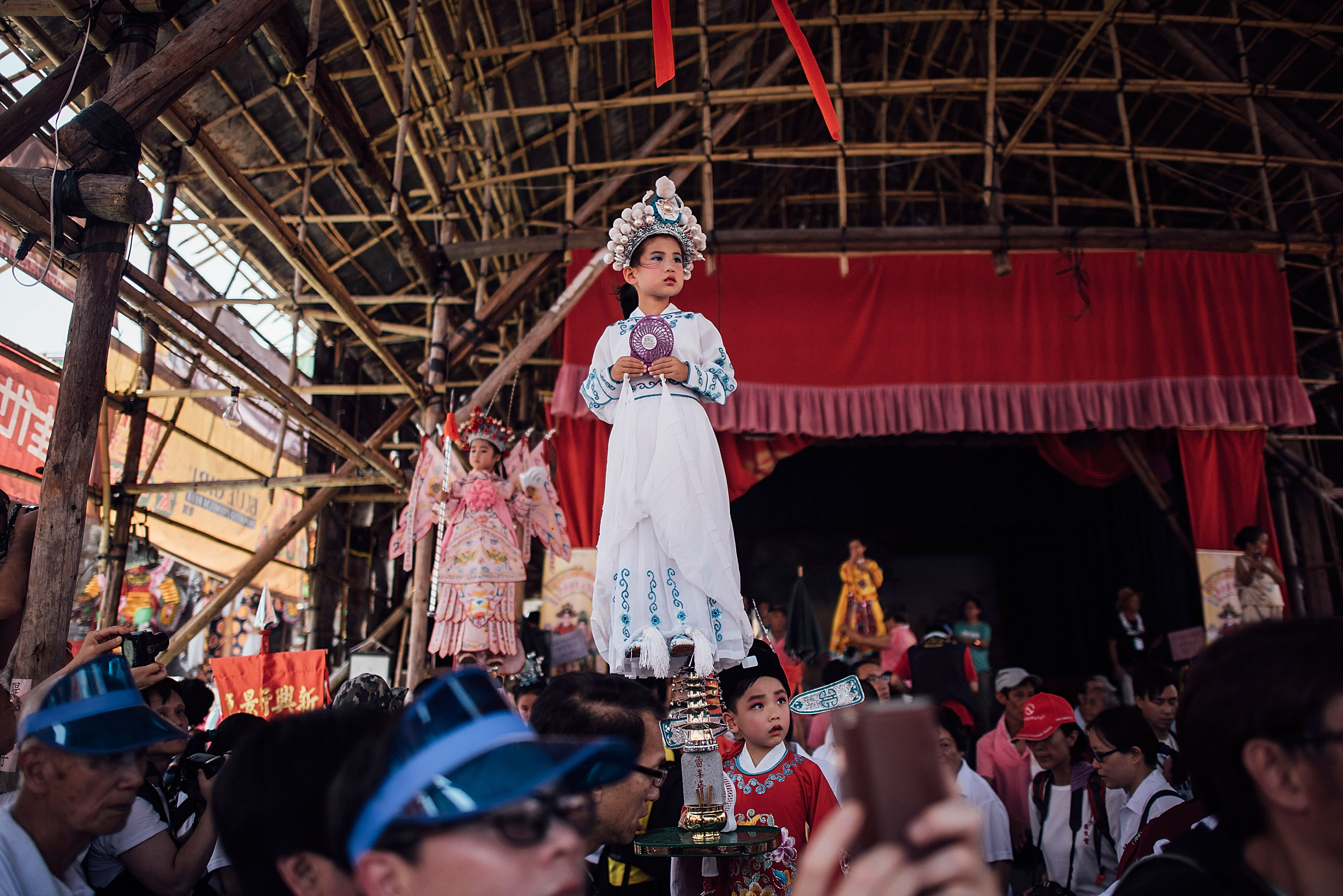 HONG KONG - MAY 25:  Children dressed in costumes perform on floats during Piu Sik (Floating Colours) Parade at Bun Festival in Cheung Chau Island on May 25, 2015 in Hong Kong. One of Hong Kong's most colourful cultural celebration events, Cheung Chau Bun Festival, will be staged on 25 May 2015 (Monday) until 26th May 2015 midnight (Tuesday). The festival has over 100 years of history. Every year, thousands of people descend upon the tiny island for The Piu Sik (Floating Colours) Parade, Lucky Bun (Ping On Bun) and The Bun Scrambling Competition, the ancient custom during the festival. The tradition has been passed down for generations. To ensure the tradition keeps passing on, every year, Cheung Chau Islanders fuse the new elements with the custom to draw the attention from the young. This year, 'K-Pop stars' will be featured by one of the Piu Sik parade teams, the first-ever 'Ping On (Lucky) Macaron' with Chinese tea favour is invented, and more to be found out on the island.  (Photo by Anthony Kwan/Getty Images for Hong Kong Images)