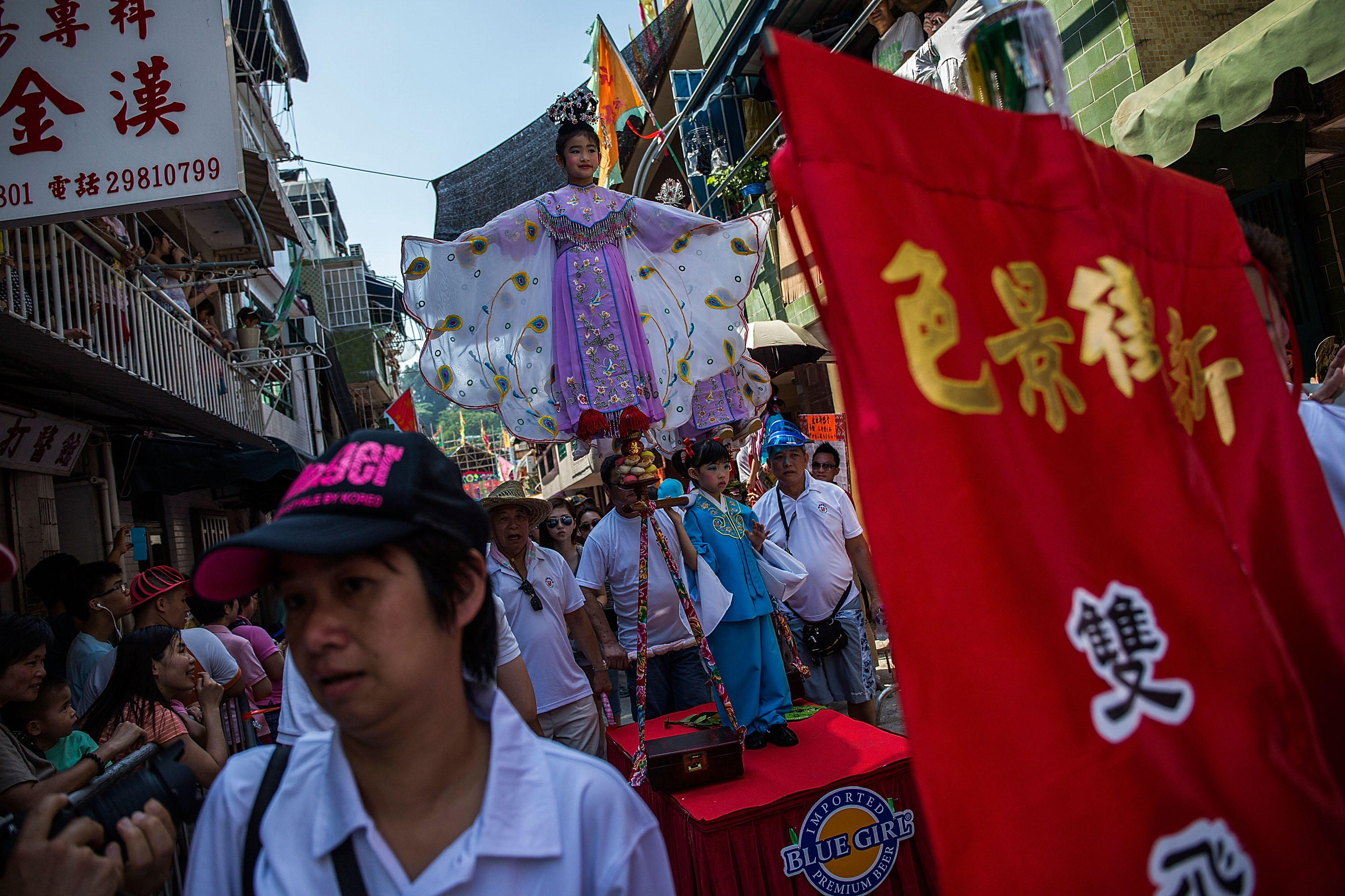 HONG KONG - MAY 25:  Children parade on a float during the Bun Festival on May 25, 2015 in Hong Kong, Hong Kong. One of Hong Kong's most colourful cultural celebration event, Cheung Chau Bun Festival, will be staged on 25 May 2015 (Monday) till 26 May 2015 midnight (Tuesday). This festival has over 100 years of history. Every year, thousands of people descend upon the tiny island for The Piu Sik (Floating Colours) Parade, Lucky Bun (Ping On Bun) and The Bun Scrambling Competition, the ancient custom during the festival. The tradition has been passed down for generations. To ensure the tradition keeps passing on, every year, Cheung Chau Islanders fuse the new elements with the custom to draw the attention from the young. This year, 'K-Pop stars' will be featured by one of the Piu Sik parade teams, the first-ever 'Ping On (Lucky) Macaron' with Chinese tea favour is invented, and more to be found out on the island.  (Photo by Lam Yik Fei/Getty Images)