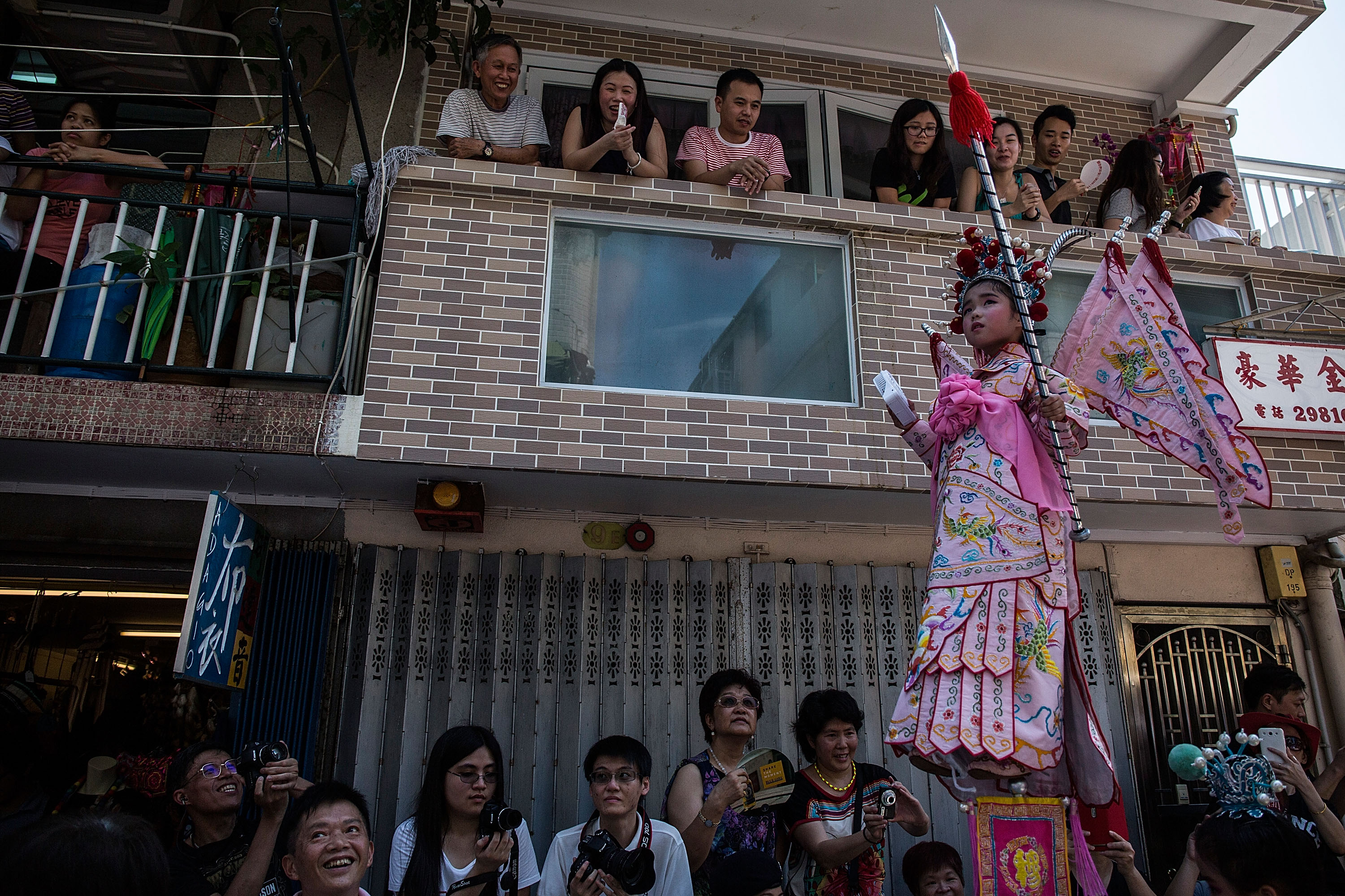 HONG KONG - MAY 25:  A child parades on a float during the Bun Festival on May 25, 2015 in Hong Kong, Hong Kong. One of Hong Kong's most colourful cultural celebration event, Cheung Chau Bun Festival, will be staged on 25 May 2015 (Monday) till 26 May 2015 midnight (Tuesday). This festival has over 100 years of history. Every year, thousands of people descend upon the tiny island for The Piu Sik (Floating Colours) Parade, Lucky Bun (Ping On Bun) and The Bun Scrambling Competition, the ancient custom during the festival. The tradition has been passed down for generations. To ensure the tradition keeps passing on, every year, Cheung Chau Islanders fuse the new elements with the custom to draw the attention from the young. This year, 'K-Pop stars' will be featured by one of the Piu Sik parade teams, the first-ever 'Ping On (Lucky) Macaron' with Chinese tea favour is invented, and more to be found out on the island.  (Photo by Lam Yik Fei/Getty Images)